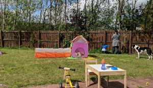 Photo of garden on a sunny day with some childrens toys lying about and a small child, mother and dog looking away from the camera in the background
