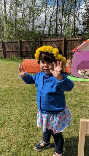 A 2 year old girl, wearing a blue cardigan and dandelion crown, stands with her hands up, all covered in rice from onigiri