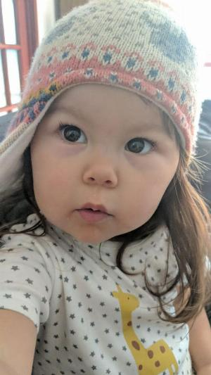 Selfie of two year old girl, wearing a woolen hat and white pajamas with a giraffe on them, accidentally posing in the style of Zoolanders blue steel