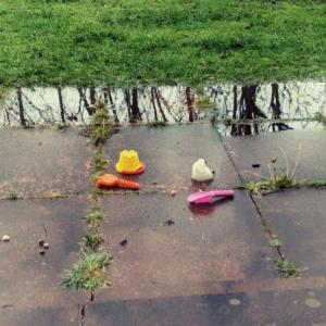 a wet, overgrown patio with a small chunk of snow, a large puddle and some toy gardening tools, formerly appendages of a snowman.