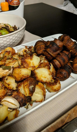 A bit plate, one half covered in very crunchy roasted potatoes, the other with vegan sausage and aubergine bacon on cocktail sticks