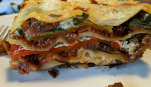 A slice of vegan lasagne, showing the layers of pasta and fillings (baked peppers, courgettes, spinach, bechamel and ragu)
