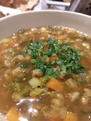 close up shot of a brownish soup with various root vegetables, barley, spinach and some fresh parsley