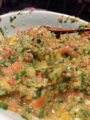 A yellow, green salsa with specks of red chillies, pretty moist looking.