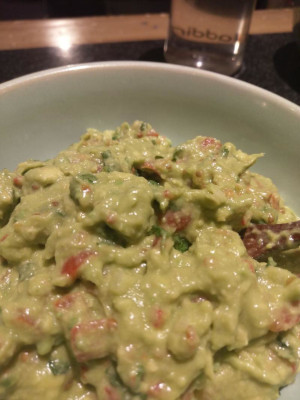 guacamole, a green avocado dish with red chillies, cherry tomatoes, peppers and fresh coriander