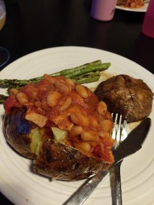 A large baked potato with crispy skin, loaded with homemade baked beans.  Behind sits a glazed Scottish flat mushroom and some grilled asparagus spears.