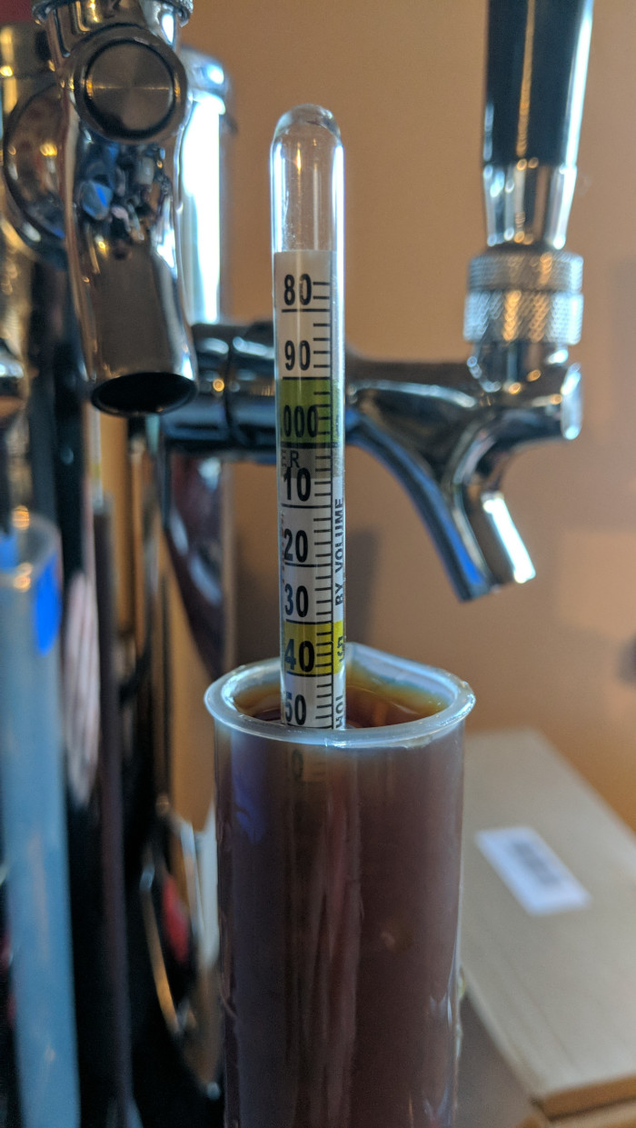 A close up of a hydrometer measuring gravity of a brown beer with some chrome bar taps in the background