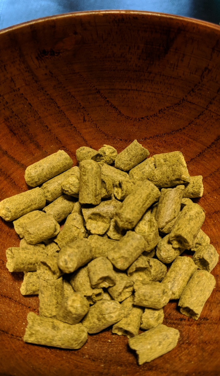 A small collection of dried, green Williamette hop pellets in a small, brown bamboo bowl
