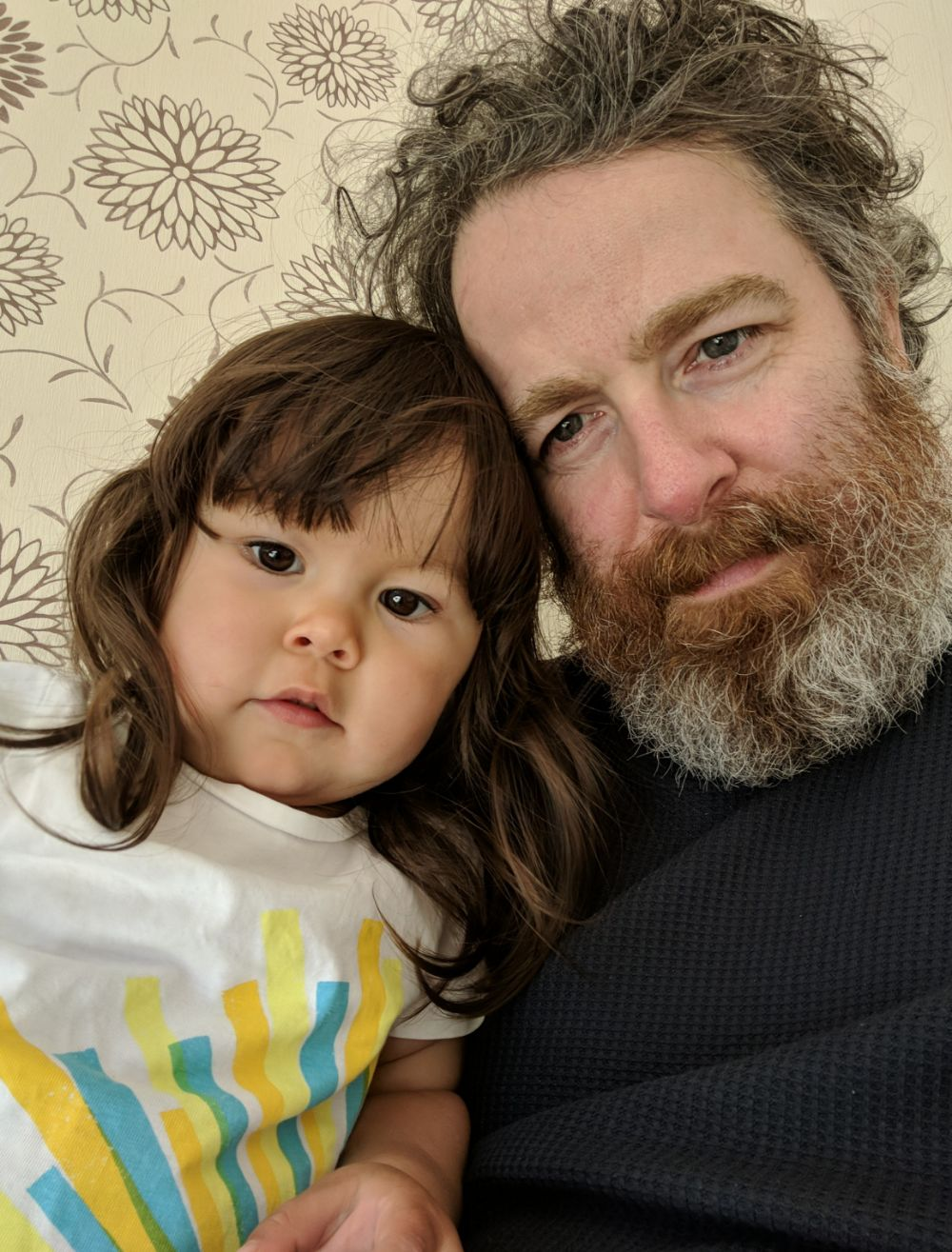 A waist up selfie of a 2 year old girl with long brown hair and a white t-shirt leaning her head against her papa, a middle-aged man with a ginger and white beard, greying straggly hair wearing a dark grey wooly jumper