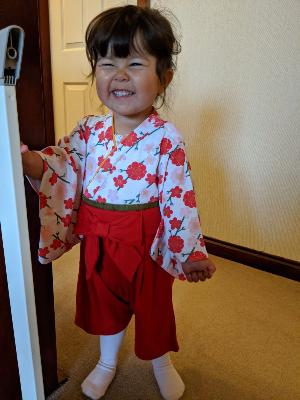 Photo of a young girl in a furisode, red on bottom, white with red flowers on top, sporting a cheeky grin
